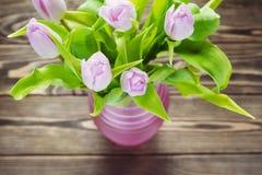 Bouquet des tulipes pourpres dans le vase rose sur une table en bois Photo stock