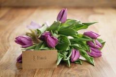 Bouquet des tulipes pourpres sur la table en bois avec la carte de papier du 8 mars Photos stock