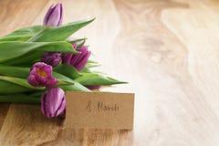 Bouquet des tulipes pourpres sur la table en bois avec la carte de voeux du 8 mars Images stock