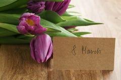 Bouquet des tulipes pourpres sur la table en bois avec la carte de voeux du 8 mars Photos libres de droits