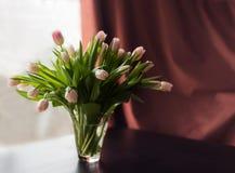 Bouquet des tulipes roses dans le vase sur la table, la fenêtre et le rideau brun comme fond Photo stock