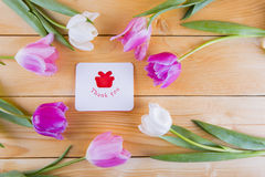 Bouquet des tulipes roses tendres avec la carte de voeux sur en bois léger Photos libres de droits