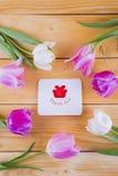 Bouquet des tulipes roses tendres avec la carte de voeux sur en bois léger Photo stock