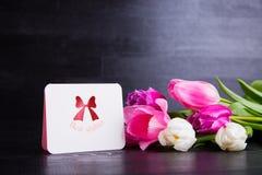 Bouquet des tulipes roses tendres avec la carte de voeux sur en bois noir Images stock