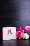 Bouquet des tulipes roses tendres avec la carte de voeux sur en bois noir Image libre de droits
