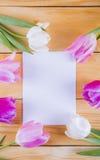 Bouquet des tulipes roses tendres avec la feuille de papier sur le woode léger Photographie stock libre de droits
