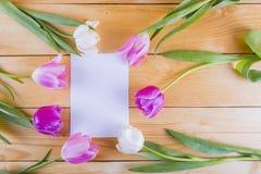 Bouquet des tulipes roses tendres avec la feuille de papier sur le woode léger Image libre de droits