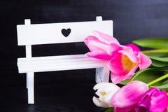 Bouquet des tulipes roses tendres avec le banc blanc sur b en bois noir Image stock