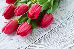 Bouquet des tulipes rouges sur la table en bois blanche Photo stock