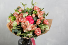 Bouquet of different flowers in a mixed arrangement against gray wall on background. Copy space Royalty Free Stock Photos