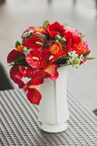 A bouquet of different red flowers in a vase on a table. Close-up. Artwork Stock Images