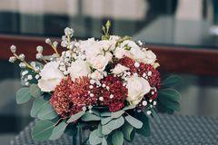 A bouquet of different white and brown flowers in a vase on a wicker table. Close-up. Artwork. Copy space. Outdoors Stock Photography