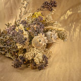 Bouquet of dried flowers on a background of gold colored cloth Stock Photos