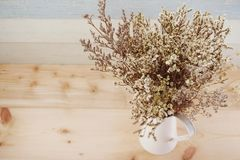 Bouquet of dried flowers bundle in metal vase home decoration. On wooden background royalty free stock images