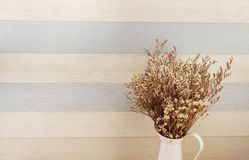 Bouquet of dried flowers bundle in metal vase home decoration. On wooden background royalty free stock photography