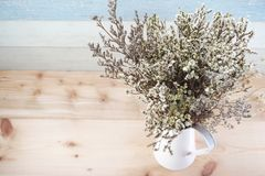 Bouquet of dried flowers bundle in metal vase home decoration. On wooden background stock images