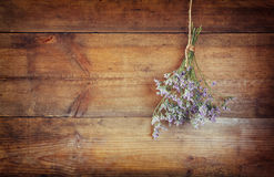 Bouquet of dried flowers hanging on rope against wooden background Stock Photography