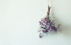 Bouquet of dried flowers hanging on rope against wooden background Stock Image