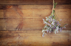 Bouquet of dried flowers hanging on rope against wooden background Royalty Free Stock Images