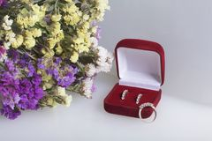 A bouquet of dried flowers lies on a white surface. Nearby is an open velvet box with a gift. Earrings and a ring for your beloved.  Stock Photography