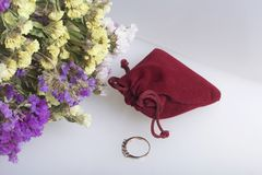 A bouquet of dried flowers lies on a white surface. Next is a velvet bag with a gift. Ring for your beloved. A bouquet of dried flowers lies on a white surface Stock Photos