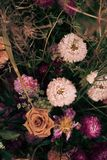 Bouquet of dried flowers on a wooden background. Beautiful withered dry flowers. Roses, Wheat and Dry Grass