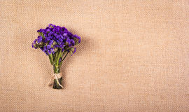 A bouquet of dried purple flowers on a natural linen background. Backgrounds and textures. A bouquet of dried purple flowers on a natural linen background royalty free stock image