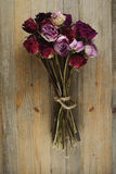 Bouquet of dried roses on a wooden background Stock Images