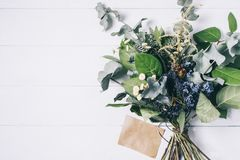 Bouquet of dried wild flowers on white table background with natural wood vintage planks wooden texture top view horizontal. Empty space for publicity stock images
