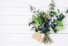 Bouquet of dried wild flowers on white table background with natural wood vintage planks wooden texture top view horizontal. Empty space for publicity royalty free stock photography