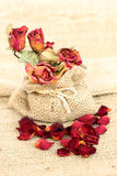 Bouquet of dried withered roses and petals over vintage sackcloth. Stock Photo