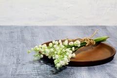 Bouquet du muguet parfumé de mai de ressort sur le plat en céramique brun sur le fond concret noir contre le mur en béton blanc photos stock