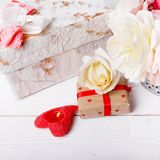 Bouquet of English rose in vase, gift, red candles in the shape of heart, ribbon. Greeting card, invitation in light Stock Images