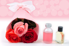Bouquet and essential oil. Rose bouquet and essential oil in front of pink blur Royalty Free Stock Photo