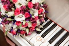 Bouquet et anneau de mariage se trouvant sur le piano blanc Photo stock