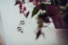 Bouquet et anneaux de mariage sur la table blanche Image stock