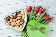 Bouquet et boîte-cadeau rouges de tulipes avec des macarons Photographie stock libre de droits