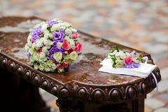 Bouquet et boutonniere nuptiales sur le banc Photographie stock libre de droits