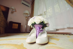 Bouquet et chaussures à la chambre d'hôtel Photos stock
