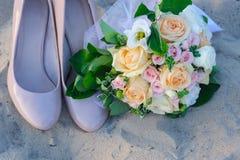 Bouquet et chaussures de mariage dans le sable Photographie stock