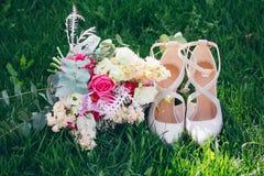 Bouquet et chaussures du ` s de jeune mariée sur l'herbe photos stock
