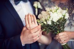 Bouquet et mains de mariage avec des anneaux Photo libre de droits