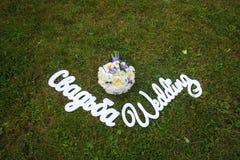 Bouquet et un mariage en bois blanc de signe sur l'herbe Photographie stock