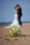 A Bouquet of Fair Roses. In front of a kissing wedding couple on the beach. The couple is blurry and the roses are sharp so the couple can preserve their Royalty Free Stock Photo