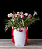 Bouquet fané des fleurs dans un boîtier blanc avec un ruban rouge sur une table en bois Sur un fond noir Photographie stock libre de droits