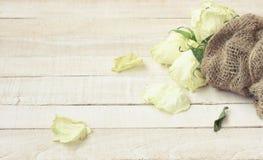 Bouquet fané des roses blanches enveloppées dans la toile à sac Photographie stock