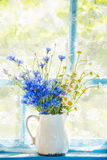 A bouquet of field flowers of cornflowers and chamomiles. In a pitcher on the window. Retro, vintage style. Home rural farming situation of the old veranda stock photo