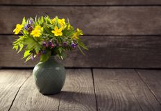 Bouquet of field wild flowers in a vase on old boards.  Stock Photos
