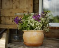 Bouquet flower clay vase wood table window outdoors village house. Window outdoors wood house bouquet flowers clay vase pot summer day stock image