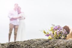Bouquet of flower with couple. Bouquet of violet and yellow flowers with couple blurred bright background Stock Photos